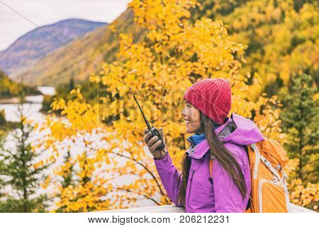 Autumn hiker camping woman talking on ham radio portable transceiver .Amateur radio operator woman speaking on handheld walkie-talking in mountains nature.