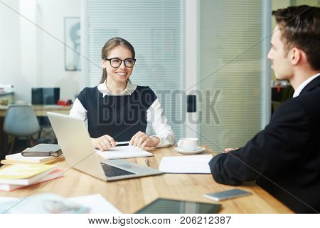 Joyful young white collar worker in eyeglasses having fun while discussing joint project with unrecognizable colleague, interior of spacious open plan office on background