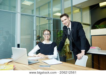 Group portrait of smiling young white collar workers posing for photography while having productive working meeting at boardroom