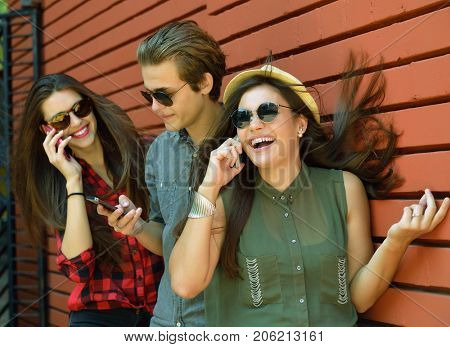 Young people having fun outdoor using gadget like a smartphone and pad against red brick wall. Urban lifestyle, internet and gadget dependence, friends, social network concept. Image toned.