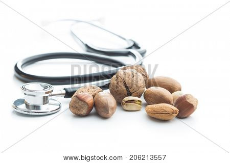 Different types of nuts in the nutshell and stethoscope. Hazelnuts, walnuts, almonds, pecan nuts and pistachio nuts isolated on white background.