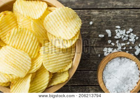 Crispy potato chips and salt in bowl. Salted potato chips. Top view.