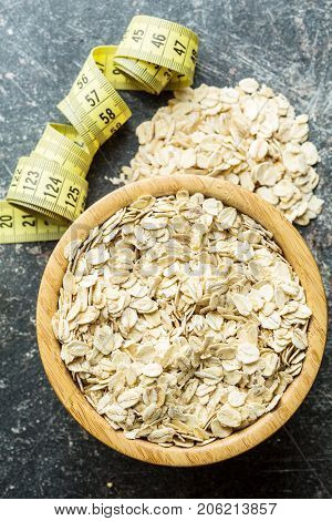 Oat flakes in bowl and measuring tape. Diet concept.
