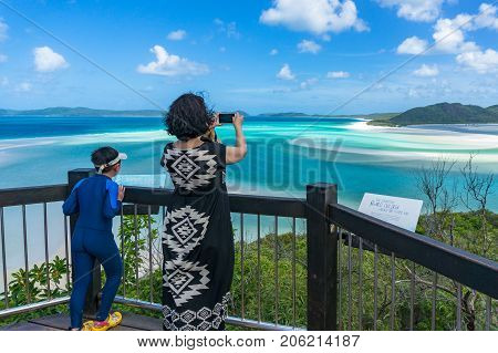 Whitsundays Australia - February 5 2017: Woman taking picture of beautiful tropical landscape with her smartphone at Hill Inlet estuary lookout