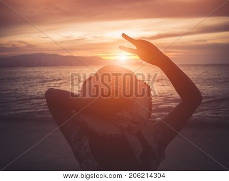 Silhouette woman holds two fingers or victory sign on the beach during sunset showing encouragement when we are discouraged.