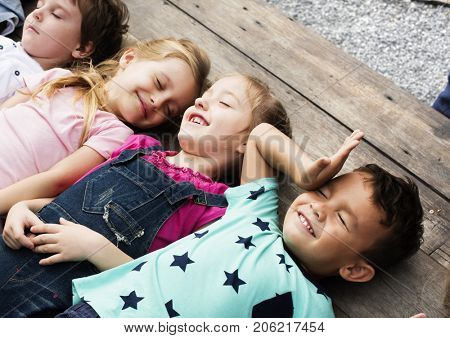 Diverse Little Kids Lay on the Wooden Floor Together