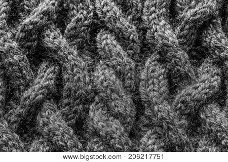 Close up of a homemade winter hat with intensive cable design in black and white.