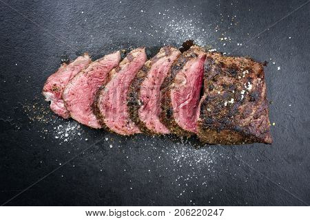 Barbecue dry aged caveman wagyu chateaubriand steak sliced as close-up on a board