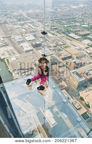 CHICAGO, IL - SEPTEMBER 2, 2017 : Little girl is standing on the ledge at the Skydeck of the Willis Tower. The Skydeck is on 103rd floor of the Willis Tower, the eighth tallest building in the world.