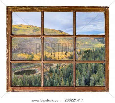 fall colors in Colorado Rocky Mountains as seen  through vintage, grunge, sash window with dirty glass