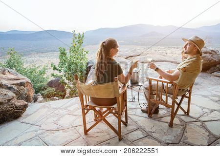 Romantic couple on safari vacation sitting outdoor at lodge enjoying stunning views over national park with glass of sundowner wine