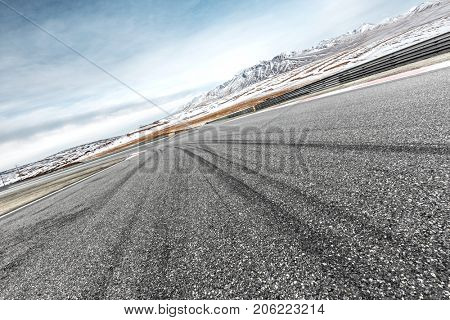 emtpy asphalt road and beautiful snow mountains in blue cloud sky