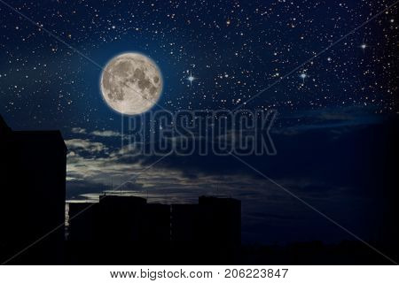 Full moon and sky with stars and  some clouds over a city