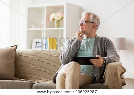 technology, old age, people and lifestyle concept - senior man with tablet pc computer sitting on sofa at home and thinking