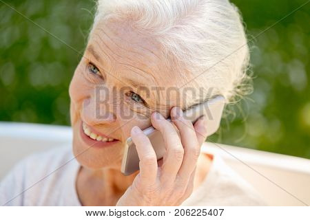 retirement, communication and old people concept - close up of happy senior woman calling on smartphone in summer