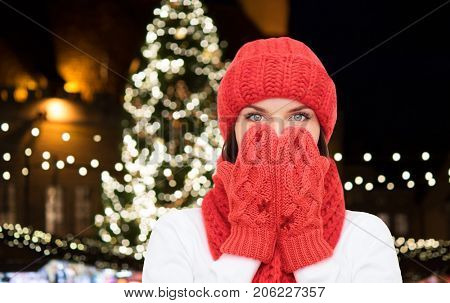 holidays and people concept - young woman in winter clothes over christmas tree lights background
