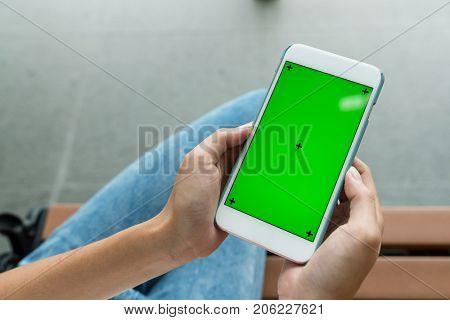 Woman holding cellphone with green chroma key