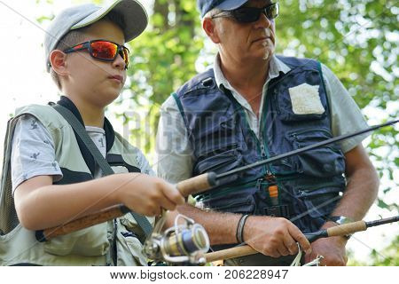 Portrait of young boy learning how to fish with daddy