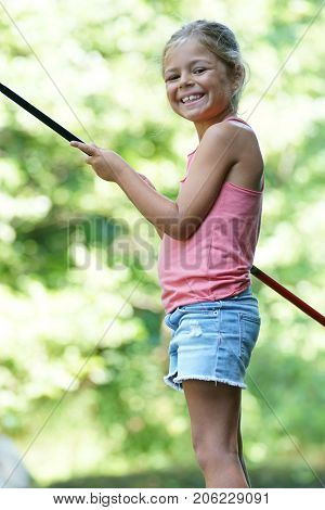 Smiling girl holding fishing line by river