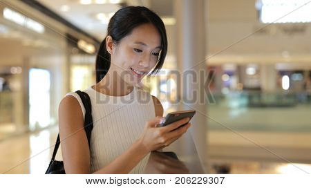 Woman using smart phone in shopping mall