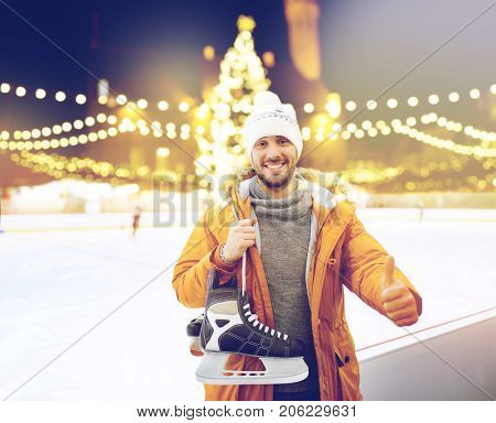 christmas and people concept - happy young man with ice-skates showing thumbs up on skating rink over outdoor holiday lights background