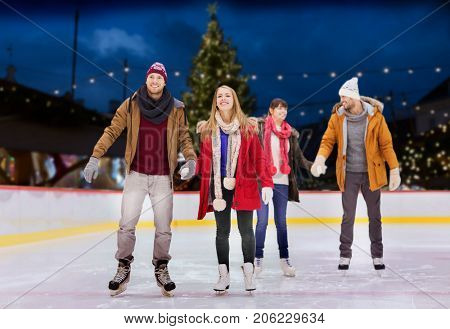 friendship, christmas and leisure concept - happy friends holding hands on skating rink over outdoor holiday lights background