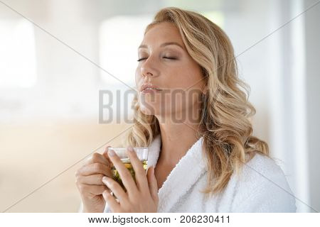 Portrait of attractive 40-year-old woman in bathrobe drinking infusion
