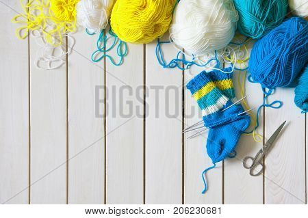 A woman knits knit socks with children's knitting needles. Stripes of turquoise yellow and white colors.