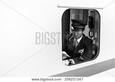 TOKYO, JAPAN - NOVEMBER 13, 2016: The conductor of Shinkansen train checking arraving time on the platform of Tokyo, Japan. Shinkansen is a high-speed railway line.