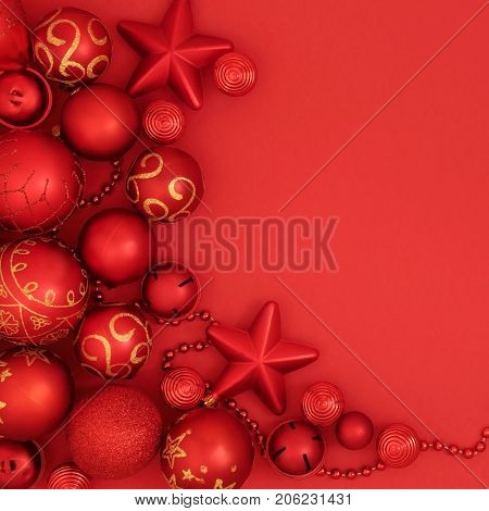 Christmas bauble decorations forming a background border with round, star shape and bead decorations on red.