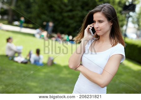 Young woman talking on mobilephone outdoors in the park.