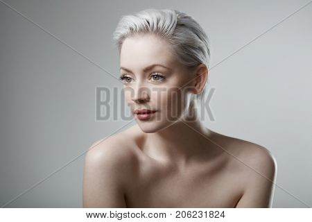 Beautiful young woman with bare shoulders looking away.