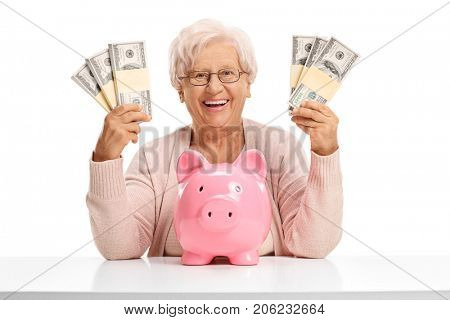 Cheerful elderly woman with a piggybank and money bundles sitting at a table and looking at the camera isolated on white background