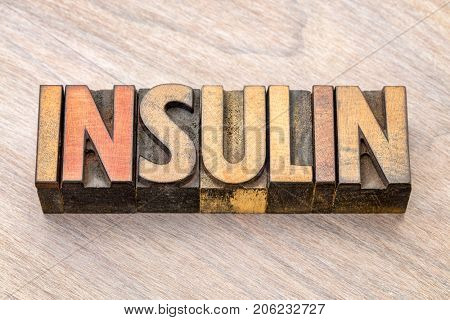 insulin word abstract in vintage letterpress wood type against grained wood