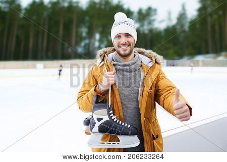 people, sport, gesture and leisure concept - happy young man with ice-skates showing thumbs up on skating rink over winter outdoor background