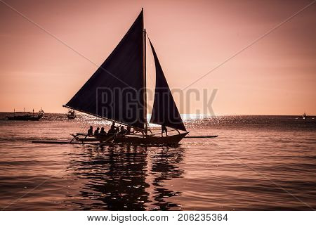 Philippine traditional boat sailing in sunset. Boracay Island, Philippines.