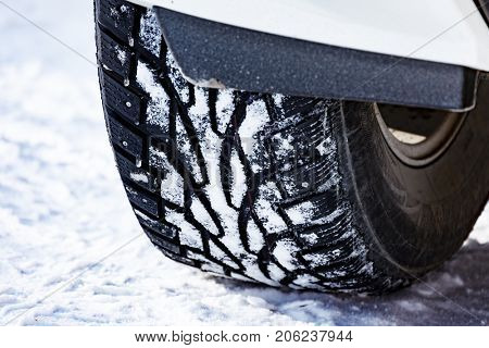 Closeup shot of automobile studded tire covered with snow at winter snowy road