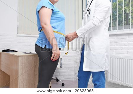 Male doctor measuring waist of overweight woman in hospital