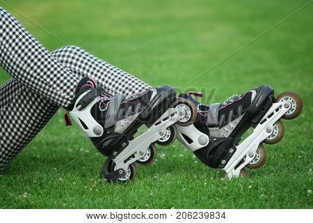Legs of young roller skater sitting on green grass