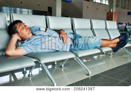 traveler with passport and ticket sleeping in airport
