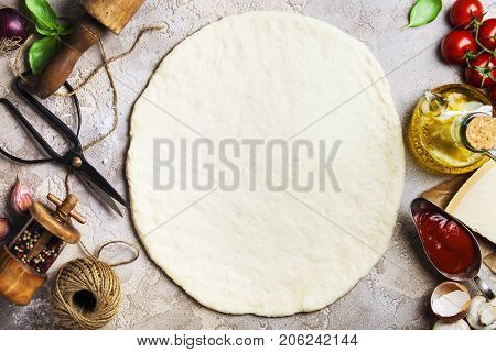 Vegetarian pizza ingredients: Raw pizza dough, olive oil, tomatoes, onion and basil leaves on the old stone surface , top view. Healthy food