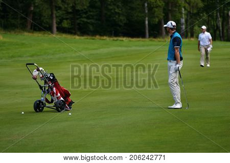 TSELEEVO, MOSCOW REGION, RUSSIA - JULY 24, 2014: Golfers on the golf course in the Tseleevo Golf & Polo Club during the M2M Russian Open. This golf tournament is the stage of the European Tour
