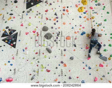 Girl climbing on a boulder wall