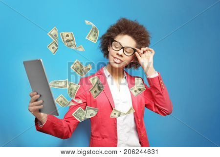 Money flying out of tablet while woman using it on blue background