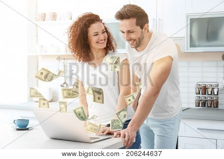 Money flying out of laptop while couple using it at table in kitchen