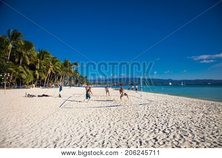 BORACAY PHILIPPINES - MARCH 17, 2016: Unknown people playing beach volleyball on the beautiful White beach of Boracay Island on March 17, 2016,  a main tourist attraction in the Philippines.