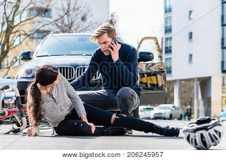 Full length view of a worried young driver calling the ambulance after hitting and injuring accidentally a female bicyclist on a city street  poster