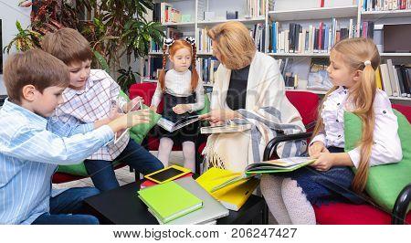 Teacher and schoolchildren at library
