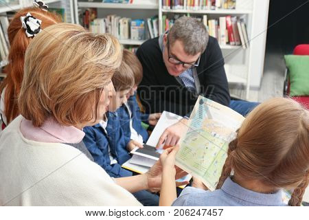 Teachers and schoolchildren with books at library