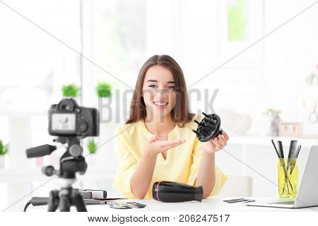 Young female blogger with diffuser recording video at home